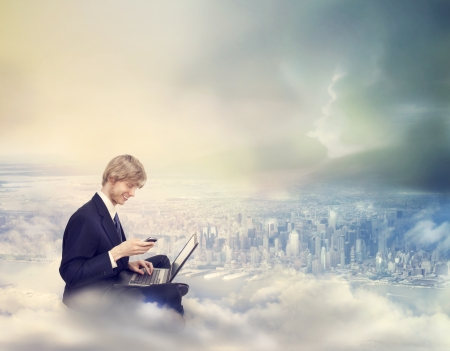 flying man: Young Business Man with Laptop and Phone on Top of the City Stock Photo