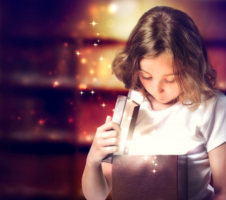 Happy Little Girl Opening a Present Box Stock Photo