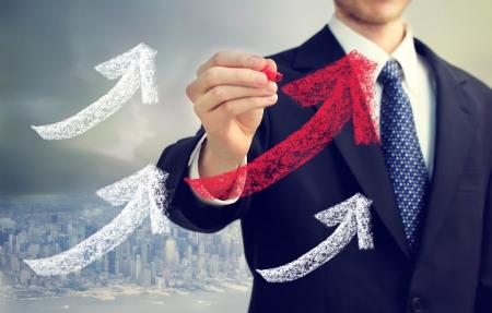 ビジネスマンの上昇の都市で矢印を描く