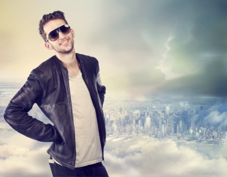 Young handsome man wearing sunglasses on top of the city photo
