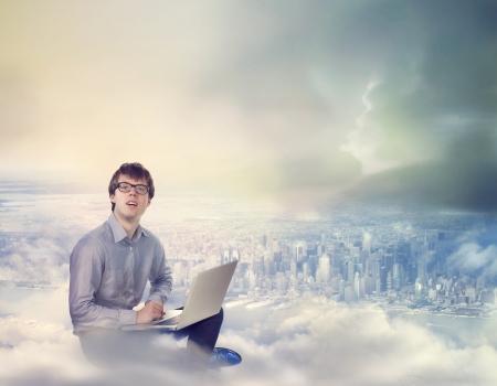 都市の上にノート パソコンを持つ男