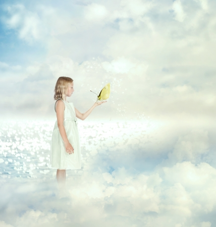 Little girl holding a butterfly on the clouds photo