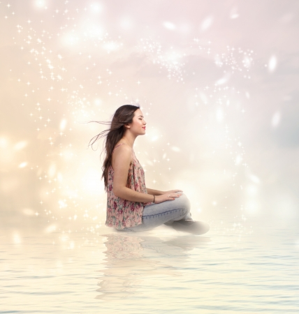 woman floating: Happy Young Woman Sitting by the Water in Pink Sky Stock Photo
