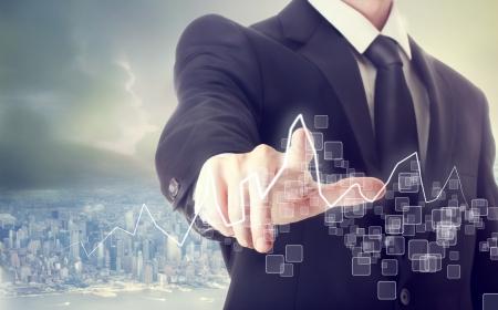 Businessman Touching a Graph above a City