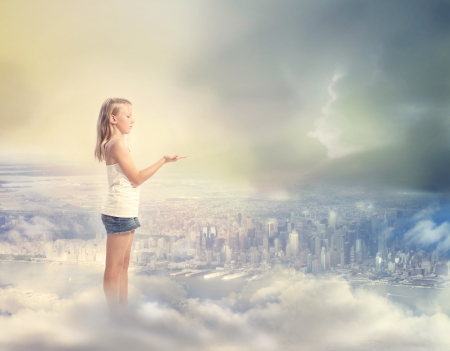 Blonde Girl  Holding Hand Out with Palm Up on the Clouds Above the City photo