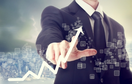 growth in economy: Businessman Touching a Graph Indicating Growth Stock Photo