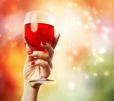 nail bar: Woman holding a wine glass on abstract lights background Stock Photo