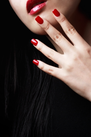 Close up of womans red nails, lips and long black hair Фото со стока