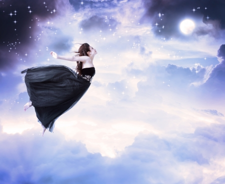 woman flying: Girl in beautiful black dress jumping in the moonlight sky (serenity) Stock Photo