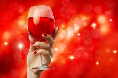 Vrouw die een glas wijn op een rode abstracte achtergrond