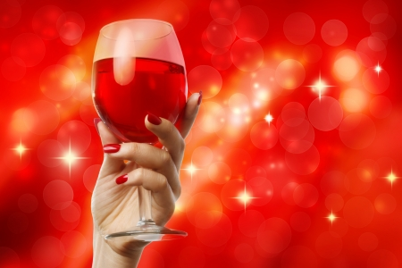 christmas manicure: Woman holding a wine glass on a red abstract background Stock Photo