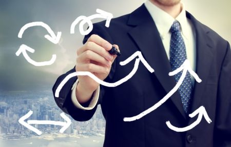 new strategy: Business man drawing arrows with city background Stock Photo