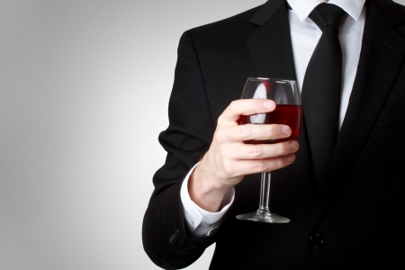 Elegant young man holding a glass of red wine  photo