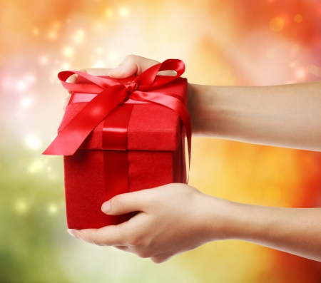 receive: Woman holding a red gift box on a bright holiday lights background