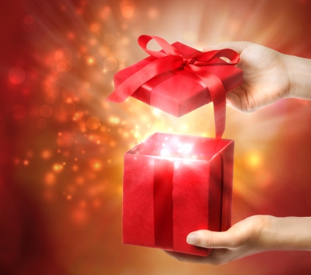 gift giving: Woman holding a red gift box on a bright holiday lights background