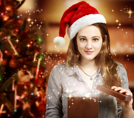 miracle tree: Happy Girl with Santa Hat Opening a Gift Box