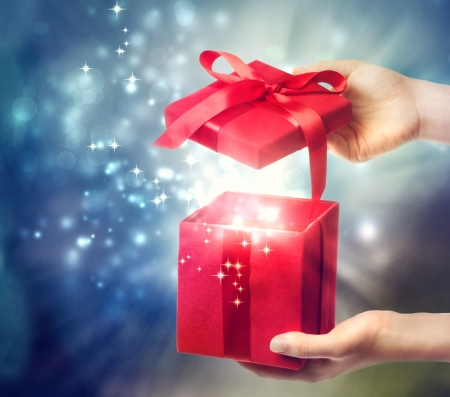 Woman holding a red gift box on a blue holiday lights background  Stock Photo