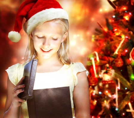 Happy Blonde Girl with Santa Hat Opening a Gift Box photo