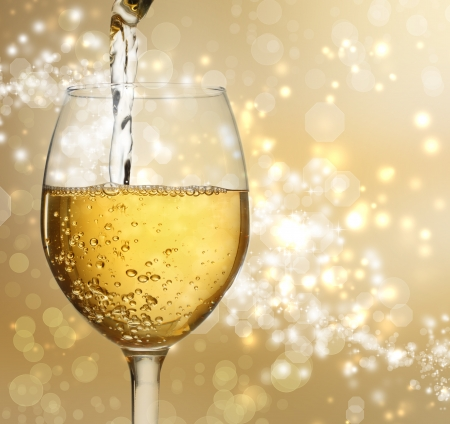 White wine being poured into a wine glass on shiny gold background photo
