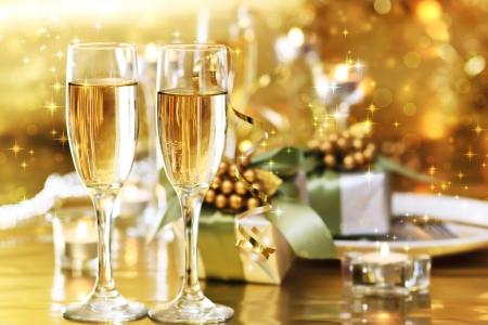 cena de navidad: Dos copas de champ�n en la mesa de la cena con cajas de regalo