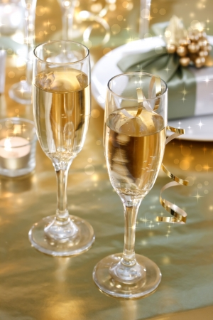 Champagne glasses on the dinner table with gift boxes photo