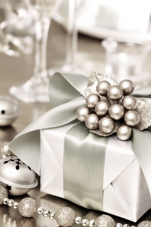 new year eve beads: Christmas Gift Box on the Dinner Table Stock Photo