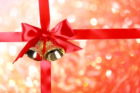 holiday greeting: Red Christmas Ribbon with Bells over Christmas Abstract Lights Stock Photo