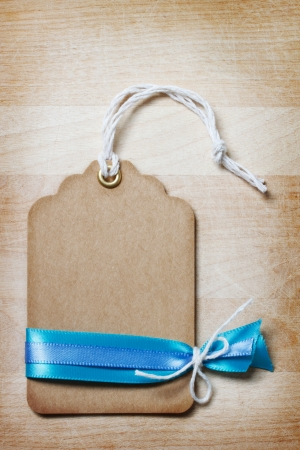 Handmade Price Tag with Ribbon and Decoration on Vintage Wooden Board
