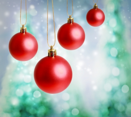Red Christmas ornaments with green-blue Christmas tree lights background Stock Photo