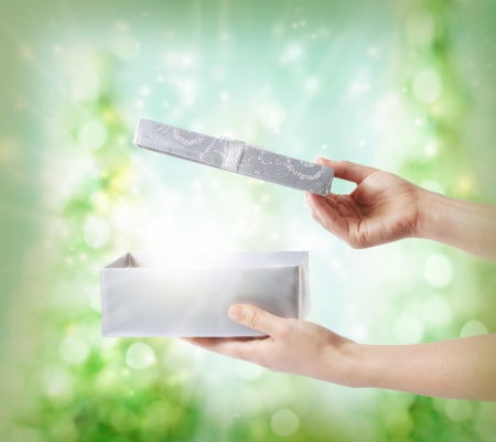dar un regalo: Mujer abriendo una caja de regalo de plata sobre un fondo verde de las luces de día de fiesta Foto de archivo