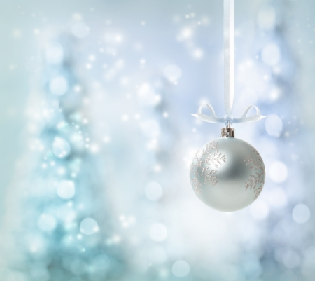 silver ribbon: Silver Christmas Ornament over glowing tree background
