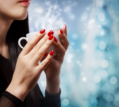 winter fashion: Beautiful woman holding a hot beverage on blue bokeh background