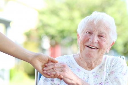 seniors homes: Happy senior woman holding hands with caretaker