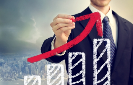 representing: Businessman with graph representing growth above the city Stock Photo