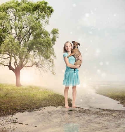 Young Blonde Girl Holding her Puppy at a Magical Brook Stock Photo