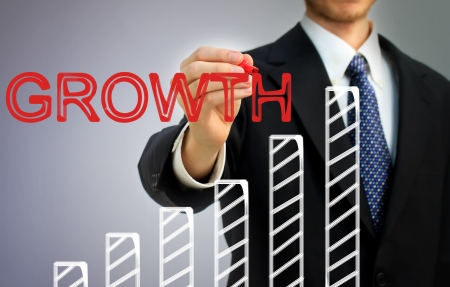 Businessman writing growth over a rising bar graph Stock Photo - 17482292
