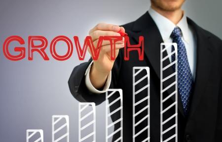 bar graph: Businessman writing growth over a rising bar graph Stock Photo