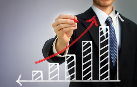 Businessman drawing a rising arrow over a bar graph photo
