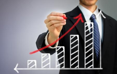 bar graph: Businessman drawing a rising arrow over a bar graph Stock Photo