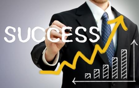bar graph: Businessman writing success with a rising arrow above a bar graph