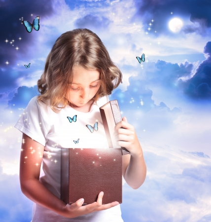 Happy Girl Opening a Box with Blue Butterflies photo