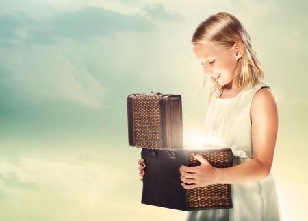 Happy Blonde Girl Opening a Treasure Box photo