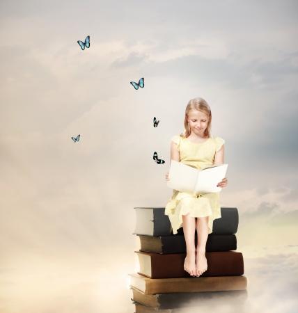 libros volando: Niña rubia que lee un libro encima de los libros Foto de archivo