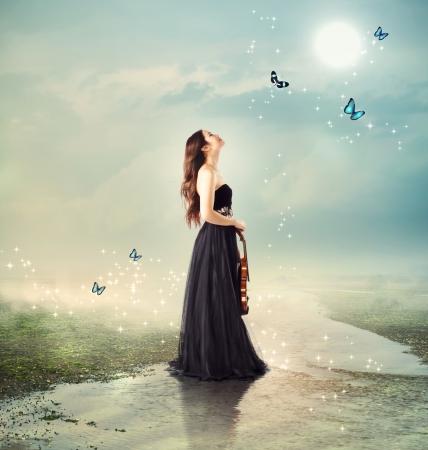 musica clasica: Violinista en un arroyo bajo la luz de la luna (con mariposas) Foto de archivo