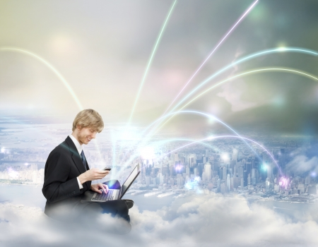 wireless communication: Young Business Man with Laptop and Phone on Top of the City - Cloud Computing