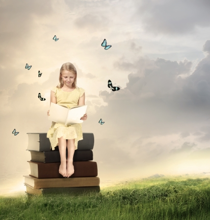 libros volando: Ni�a rubia que lee un libro encima de los libros Foto de archivo