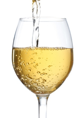 White wine being poured into a wine glass on white background Stock Photo
