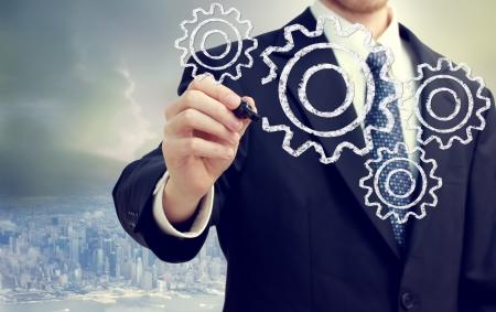 interlocking: Businessman with gears - concepts of teamwork, efficiency, interlocking parts.