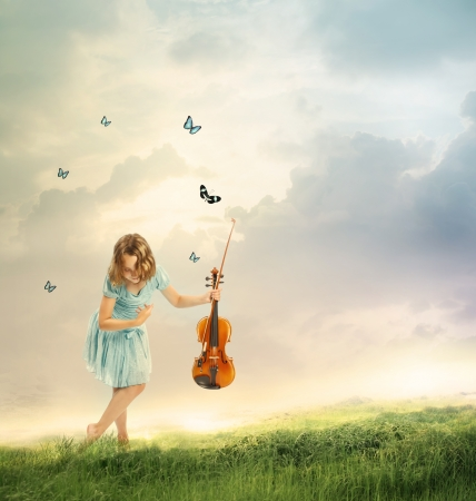 Little girl with a violin in a fantasy landscape with butterflies