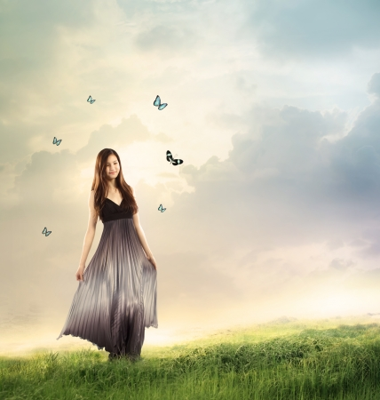 fantasy: Young woman in a beautiful silver dress in a fantasy landscape with butterflies  Stock Photo